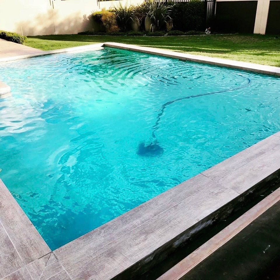 Laminated Miter Edge for pool coping in wood-llook porcelain tile.
